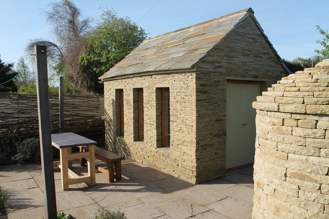 stone summer house with dining area