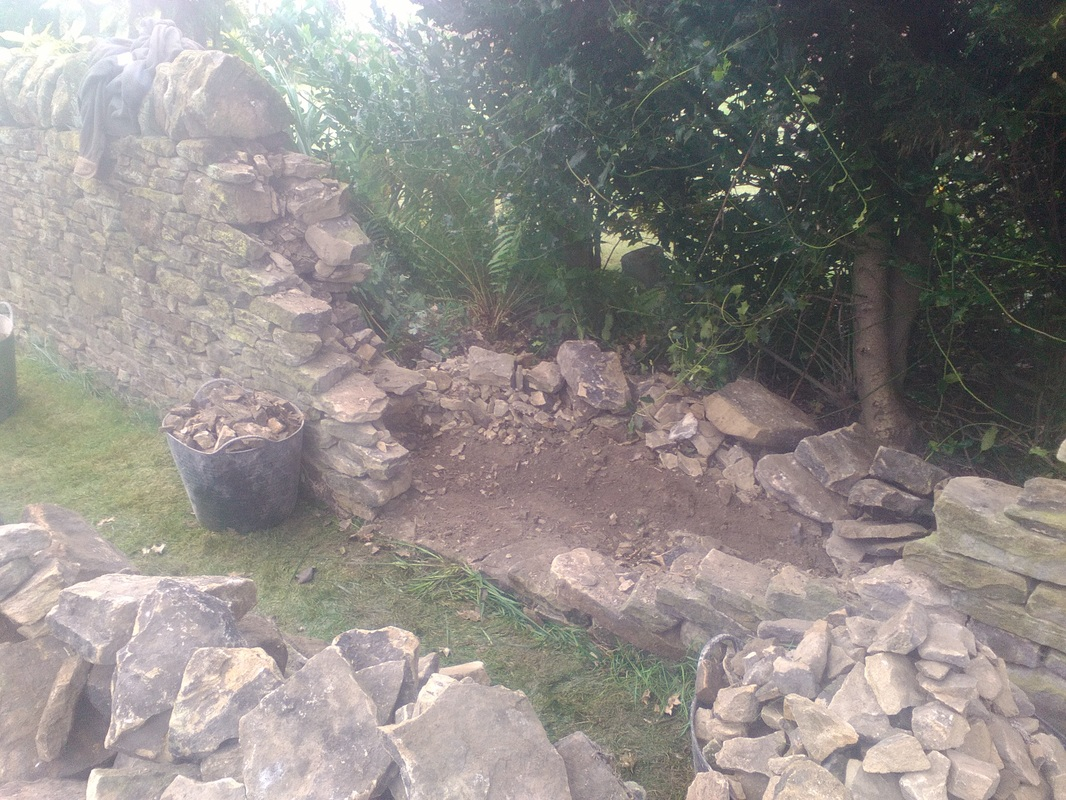 collapsed section of wall stripped back in a large v shape back to sound wall